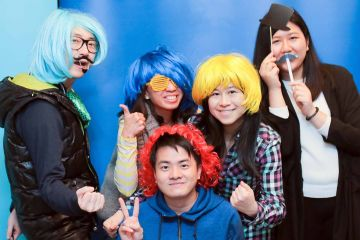 five people wearing wigs and funny accessories unny wig and a big bow tie in the picture fun team building activity