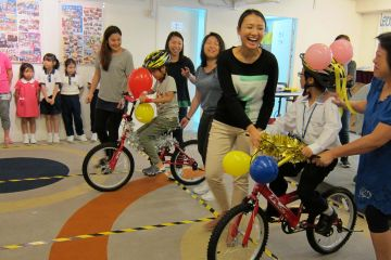 smiling women give newly built bikes to happy children