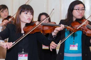 women playing violin crescendo musical team building activity