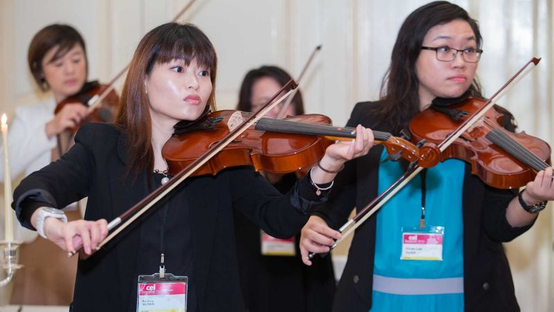 women playing violin crescendo musical team building activity