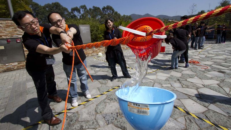 employees collaborate to complete breakthrough team building activity outdoors