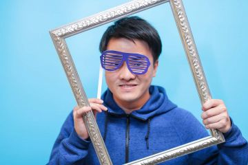 man with funny glasses holding a frame to his face unny wig and a big bow tie in the picture fun team building activity