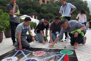 employees collaborate to complete breakthrough team building activity