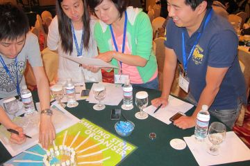 team collaborate to complete essence of excellence team building activity