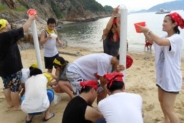 employees collaborate to complete breakthrough team building activity on a beach