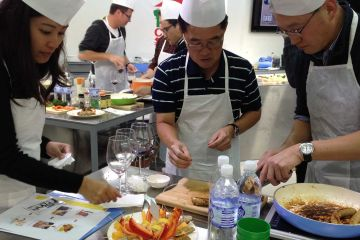 team collaborate to complete cooking team building activity sausage sensation
