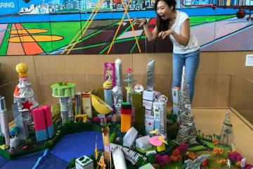 woman posing by a model of the city team building activity city build