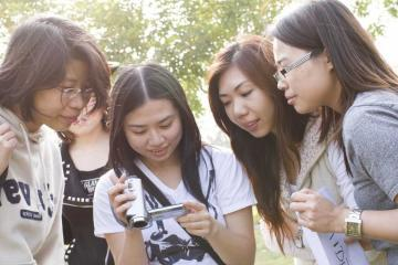 women checking recording of thei hollywood challenge team building task singapore