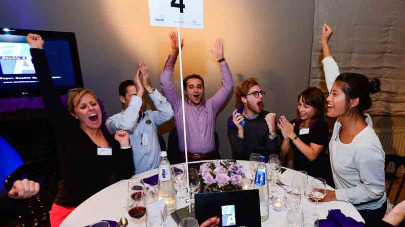 people sat around a conference table during dinner cheering at a team building activity