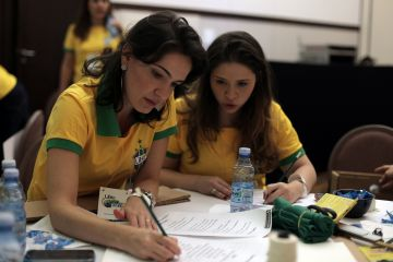 Two women sat at a table with yellow and green shirts on discussing tactics in Catalyst team building activity Goall!!