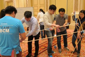 employees collaborate to complete bridging the divide creative team building activity