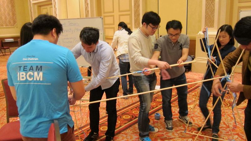 employees collaborate to complete innovative team building programme