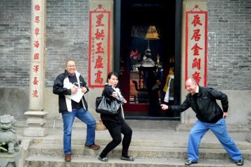 team striking a funny pose outside a building during travel show outdoor team building activity