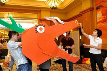 three people cooperating to create a dragons head in Catalyst teambuilding activity Dragons Squad