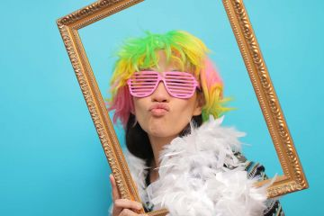woman with wig pouting holding a picture frame to her face