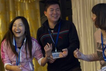 three people laughing having fun one voice team building activity