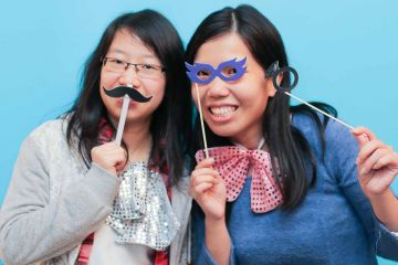 two women posing with funny accessories unny wig and a big bow tie in the picture fun team building activity