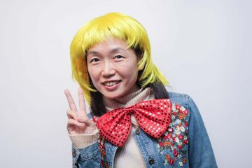 woman wearing blond funny wig and a big bow tie in the picture fun team building activity