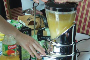 Hand on a blender start button mixing juices in the business game Creative Juices by Catalyst Global