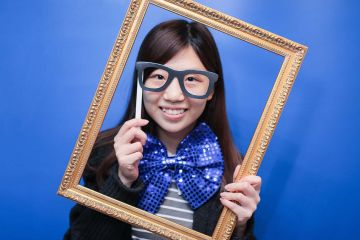 woman holding a frame to her face unny wig and a big bow tie in the picture fun team building activity