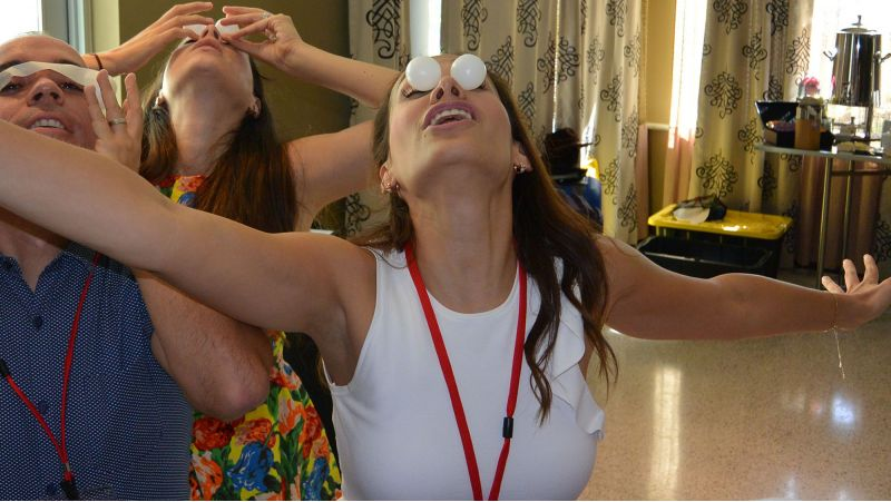 three people having fun with pinpong balls on their eyes in quickfire game