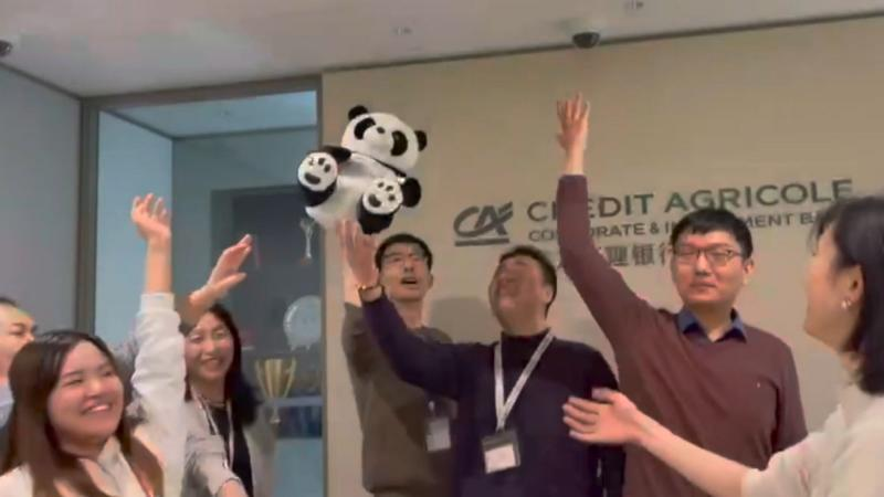 Team in front of Credit Agricole logo throwing Panda in the air for collaboration