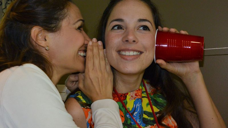 two women communicating via a cup phone in team building game quickfire