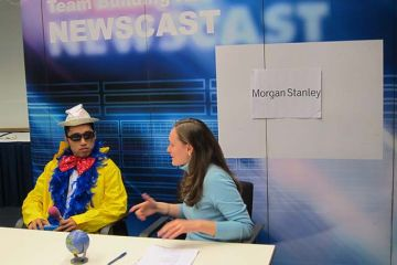 man in funny clothes and a woman interviewing him news cast team building activity