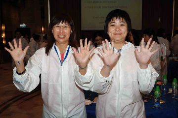 two women show their hands with paint on creative team building activity