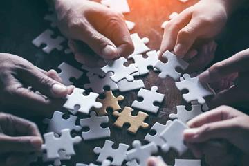 people holding a piece of a jigsaw