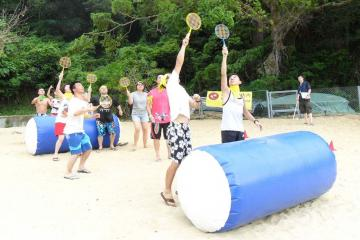 team in action to complete team building challenges beach