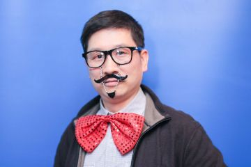 man wearing funny mustache and big bow tie unny wig and a big bow tie in the picture fun team building activity