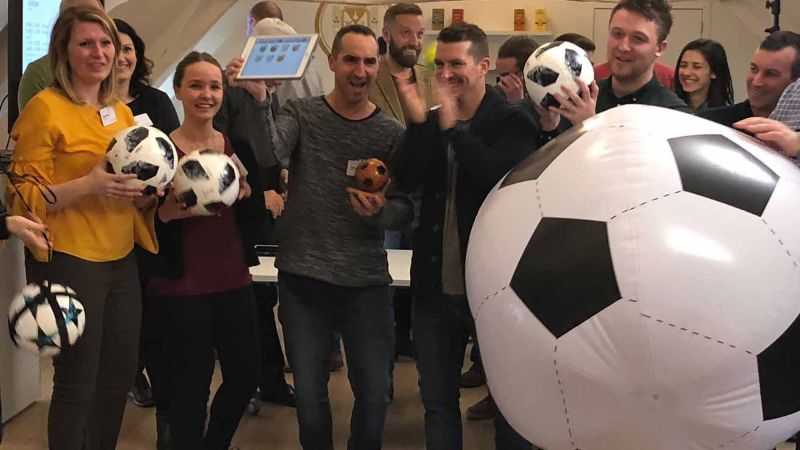 group of people playing team building indoor soccer activity quickfire